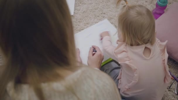 Top view of young Caucasian woman and little baby girl drawing with colorful pencils. Mother playing and educating her adorable daughter. Joy of maternity. Shooting over the shoulder.