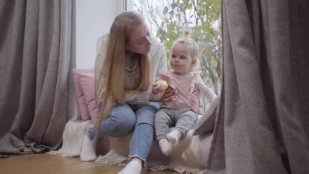 Close-up of happy Caucasian young mother kissing her lovely baby daughter on cheek and smiling. Little blond girl sitting with mom at windowsill and eating apple. Happy childhood, joy of maternity.