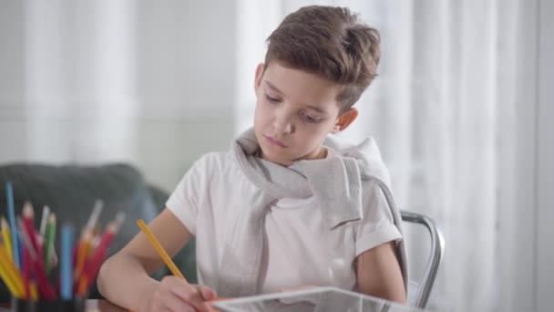 Portrait of concentrated Caucasian boy sitting at the table and drawing or writing in notebook. Schoolboy doing homework at home. Education, intelligence, bright mind, generation z
