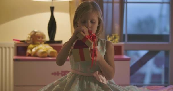 Közelkép kaukázusi lány nyitó koporsó elegáns íj és levesz valami pirosat. Kisgyerek, gyönyörű ruhában, otthon ül a szobájában. Gyermekkor, szabadidő, ajándék.