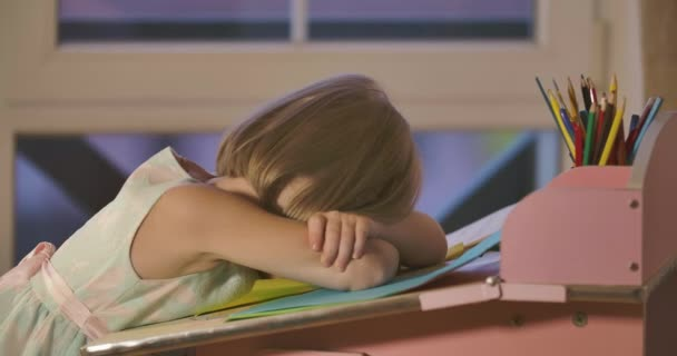 Exhausted Caucasian blond girl in elegant dress with butterflies sleeping at the desk. Schoolchild tired after doing homework at home. Education, studying, generation Z.