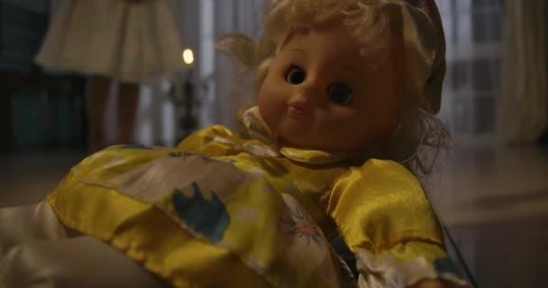 Malá běloška pomalu přichází k panence ležící na podlaze ve světle svíček. Strach, strach, podivnost.
