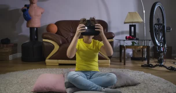 Portrait of teenage Caucasian boy in VR headset sitting on the floor at home and looking around. Nice child trying on his gift. Virtual reality, 3d, modern technologies. Cinema 4k ProRes HQ.