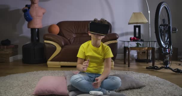 Curly-haired teenage boy in VR googles moving his hands and looking around. Caucasian schoolboy in casual clothes using augmented reality headset at home. Generation Z. Cinema 4k ProRes HQ.