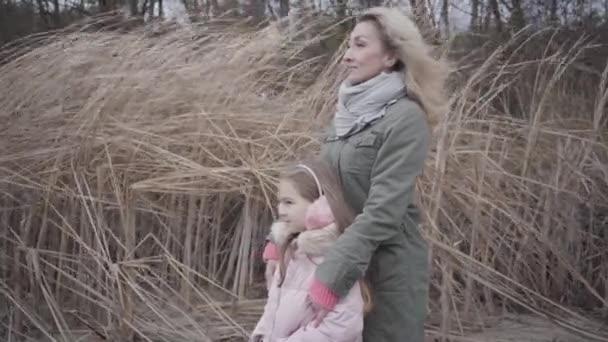 Kis kaukázusi lány rózsaszín alkalmi ruhában, szélben állva az anyjával. Mosolygó nő és a lánya félrenéznek és beszélgetnek. Szabadidő, szabadidő, őszi tevékenységek.