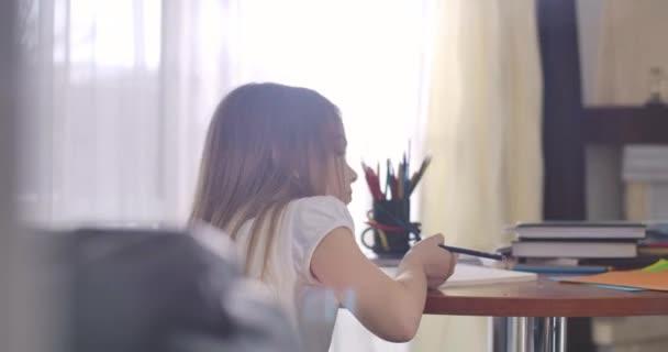 Közelkép a kimerült kaukázusi iskolás lányról, aki napsugarakban ül az asztalnál. Fáradt gyerek feküdt fejjel a füzetben, és csukott szemmel. Túlhajszolt, tanult, tanult. Mozi 4k Prores Hq