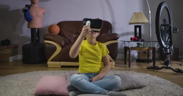 Young Caucasian teen with curly hair in VR headset holding remote control and looking around. Child using virtual reality. Augmented reality, VR glasses, generation Z. Cinema 4k ProRes HQ.