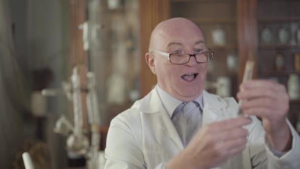 Glücklicher alter Mann mit Brille, der auf das Reagenzglas blickt und aufgeregt lächelt. Reife Apotheker gründeten neue Medizin in alten Apotheken. Retro, Vintage, Medizin, Gesundheitswesen.