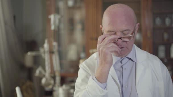 Porträt eines aufgebrachten kaukasischen Seniors, der die Brille abnimmt und emotional spricht. Trauriger oder wütender reifer Kerl in weißer Robe, der in einer alten Drogerie steht. Vintage, Retro.