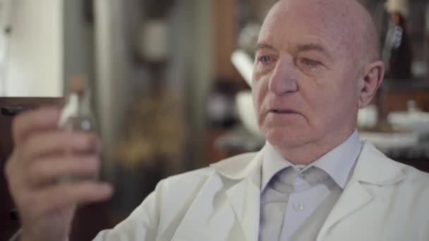 Großaufnahme des weinenden alten Mannes, der auf ein Fläschchen mit Flüssigkeit blickt. Reife kaukasische Apotheker im weißen Gewand schafften es nicht, Leben zu retten. Porträt eines einsamen depressiven Typen in der Vintage-Drogerie.