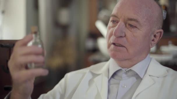 Porträt eines alten Mannes mit Tränen in den Augen, der eine Flasche mit Flüssigkeit betrachtet. Der Schwerpunkt liegt auf der alten Medizin. Porträt eines einsamen depressiven kaukasischen Apothekers in einer alten Drogerie.