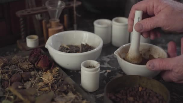 Close-up of table with dried flowers and vintage chemical containers. Old male Caucasian hands grinding powder using mortar and pestle. Ancient apothecary, alternative medicine, retro, healthcare.