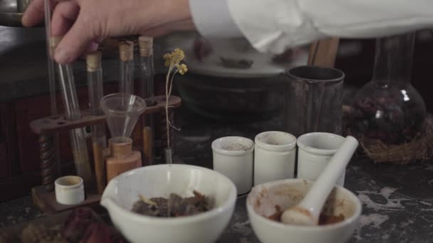 Close-up of Caucasian male hand touching ancient test tubes. Mortar and pestle standing at the table with different vintage chemical ingredients. Healthcare, alternative medicine, retro, vintage.