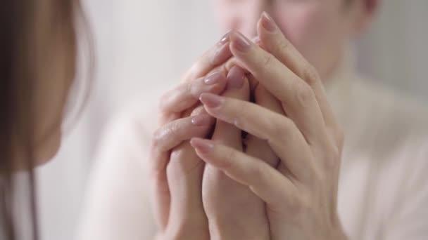 Dvě rozmazané ženy si povídaly a držely se za ruce. Matka a dcera, péče, jednota.