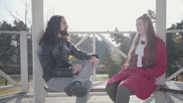 Fiatal boldog férfi és nő ül a pavilonban az őszi parkban és beszél. Hippi barát és barátnő randiznak a szabadban. Mosolygó multiracionális pár élvezi napsütéses nap együtt.