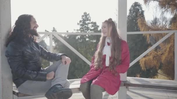 Egy vidám fiatal biraciális pár portréja, akik a pavilonban ülnek a padon, beszélgetnek és nevetnek. Pozitív hippi férfi és nő randiznak az őszi parkban. Szerelem, romantika, boldogság, öröm, szabadidő.
