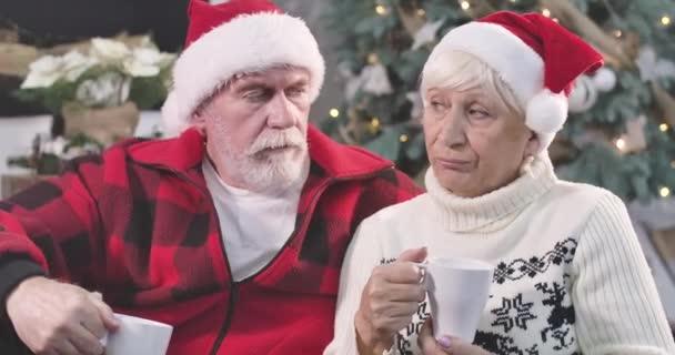 Detailní záběr portrét rozrušený dospělé bělošky muž a žena sedí s kávou na pozadí zdobené vánoční stromeček. Starý pár čeká na děti na Silvestra. Cinema 4k Prores Hq.
