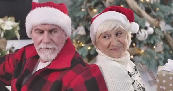 A boldog, érett kaukázusi pár közeli arcai hátradőlnek, a kamerába néznek és mosolyognak. Karácsony, szilveszter, örök szerelem, ünnepek. Mozi 4k Prores Hq.