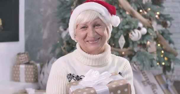 Detailní portrét pozitivní starší bělošky držící vánoční dárkovou krabici, dívající se do kamery a usmívající se. Krásná stará dáma tráví Silvestra doma. Cinema 4k Prores Hq.