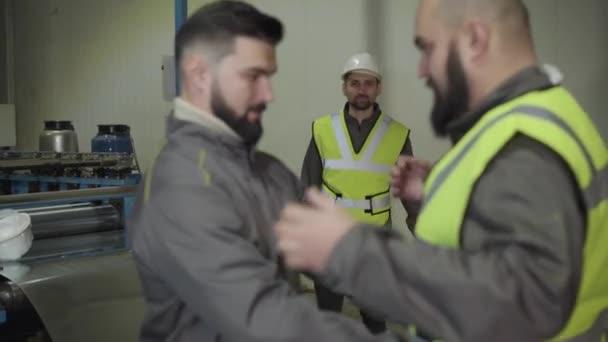 Mladý bělošský předák kontroluje vestu na vousatém dělníkovi. Muž v ochranné přilbě se táhne v pozadí. Pracovníci ve výrobním závodě. Bezpečnost, výroba, mlýn, profese, povolání.