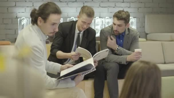 Mladí běloši sedí s dokumenty v otevřeném prostoru a diskutují o projektu. Tvůrčí kolegové mají brainstorm. Moderní životní styl, spolupráce, kancelář, obchod, kreativita.