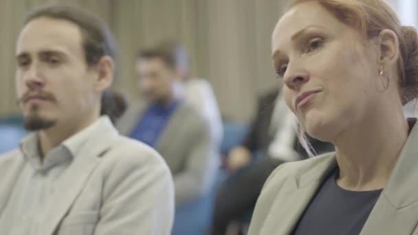 Mladí bělošští kancelářští pracovníci sedící v konferenční zóně, naslouchající řečníkům a diskutující o projektech. Kolegové mají obchodní schůzku v otevřené kanceláři. Kreativita, inovace, týmová práce.