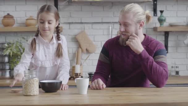 Csinos kaukázusi barna lány fonott copfokkal, kukoricapelyhet öntött a tányérba, és odaadta apának. A lánya reggelit főz a felnőtt férfinak. Gondozás, boldogság, jó kapcsolat.