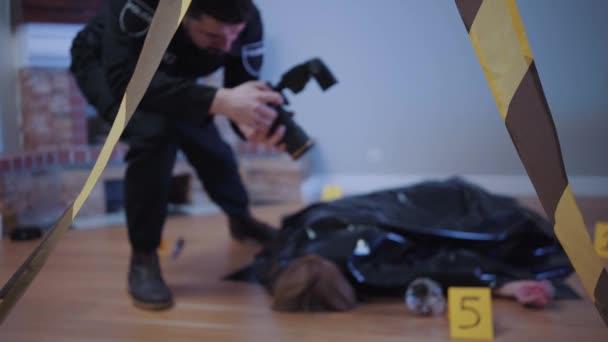 Rozmazaný bělošský detektiv otvírající tělo oběti vraždy a fotografující. Soustředí se na policejní pásku v popředí. Detektive, vyšetřování, místo činu.