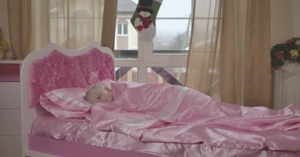 Portrét roztomilé bělošky spící v růžové posteli. Klidné dítě odpočívající ráno ve svém pokoji. Dětství, klid, krása. Cinema 4k Prores Hq.