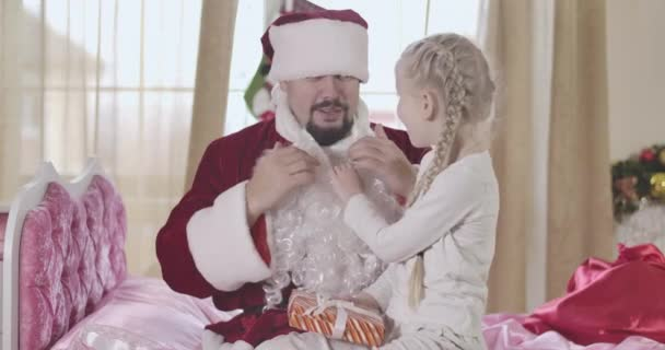 Roztomilé běloška s copánky drží falešné vousy s rukou jako muž v kostýmu Santa Clause drží ji na kolenou. Pozitivní otec překvapuje svou dceru na Silvestra. Cinema 4k Prores Hq.