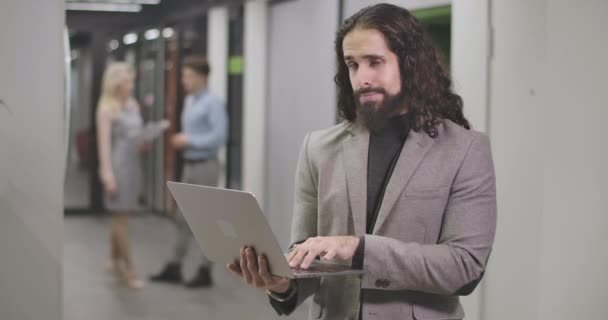 Portrait of bearded Middle Eastern man typing on laptop keyboard, looking at camera and smiling. Confident office worker standing in open space. Business, success, hardworking. Cinema 4k ProRes HQ.