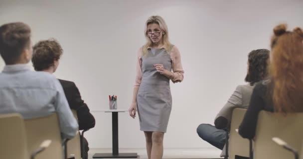 Magabiztos fehér felnőtt nő szemüvegben, kollégák előtt áll és beszél. A csapat üzleti projektről tárgyal a nyílt űrirodában. Mozi 4k Prores Hq.