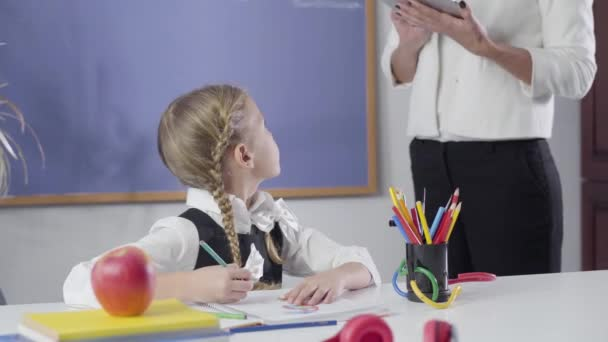 Smart Caucasian girl with pigtails looking back at unrecognizable tutor and writing in exercise book. Schoolchild studying at home. Private education, diligence, learning.