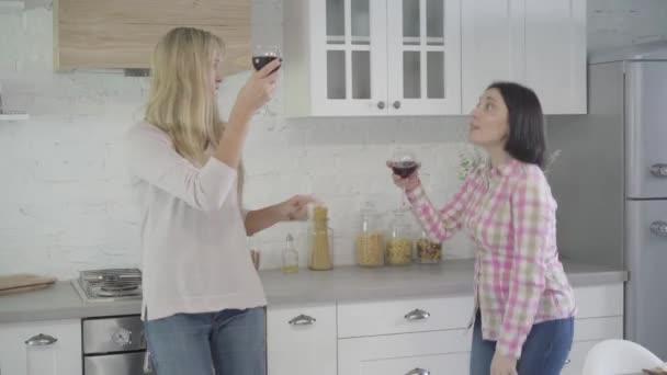 Portrét veselých dospělých bělošek tančících v moderní kuchyni, cinkajících skleničkách a pití. Dvě kamarádky se baví o víkendech doma. Volný čas, štěstí, životní styl.