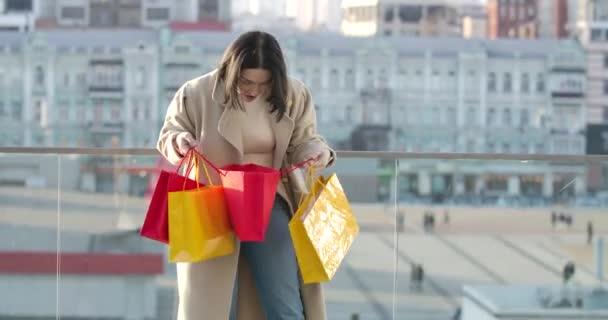 Elégedett kaukázusi nő, színes bevásárló táskákba néz és mosolyog. Fiatal női bolti mániákus, aki a város utcáján áll vásárlással. Üzlet, életstílus. Mozi 4k Prores Hq.