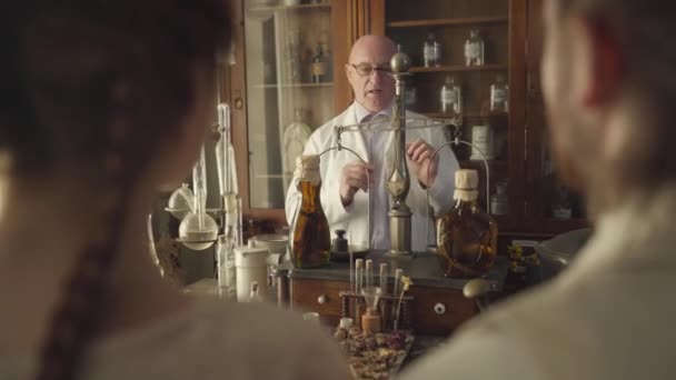 Mature Caucasian man standing at the table with vintage flasks, test tubes, vintage weighting machine, and talking. Shooting over shoulder. Chemical terms written on bottles.