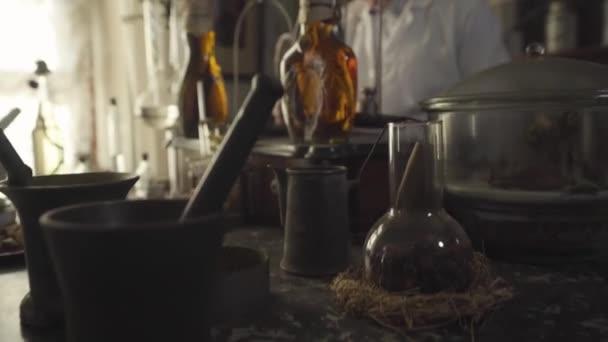 Porträt eines alten kaukasischen Mannes mit Glatze, der antike Flaschen, Behälter und Reagenzgläser überprüft und mit Federstift schreibt. Apotheker aus dem 19. Jahrhundert überarbeitet alte Apotheke. Retro-Stil, Gesundheitswesen