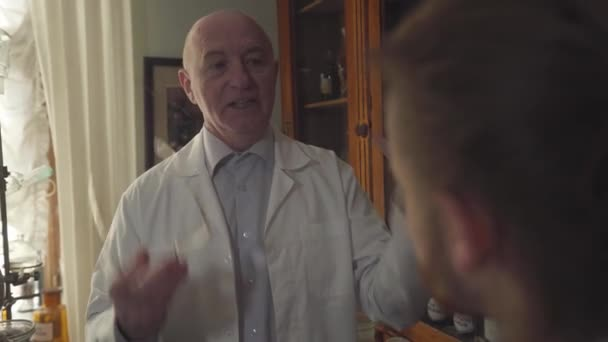Close-up of mature Caucasian man in white robe talking emotionally to young man at the foreground. Old pharmacist educating worker in old-fashioned drugstore. Chemical terms written on bottles.