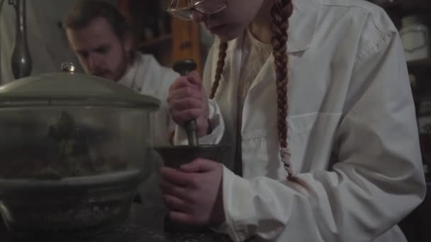 Camera moving up from female Caucasian hands grinding medicine using mortar and pestle to face of young woman. Cute girl working in ancient drugstore with male colleague.