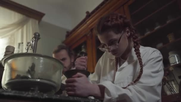 Portrait of concentrated Caucasian girl with red pigtails grinding medicines in ancient pharmacy. Serious-looking woman working hard in vintage drugstore. 19th century.