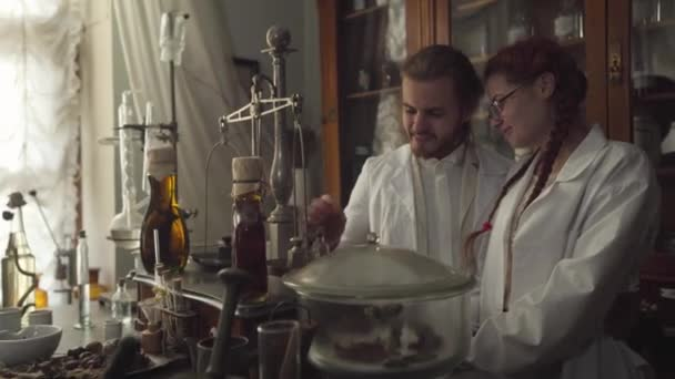 Portrait of smiling Caucasian man and woman looking at ancient flask with transparent liquid. Two pharmacists discovered medicine in retro drugstore. Focus changes from faces to bottle.