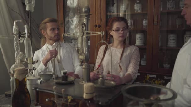 Old Caucasian man on the right talking with young guy and girl. Younger pharmacists asking advice from their older colleague. People working in ancient drugstore. Chemical terms written on bottles.