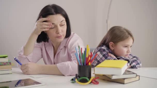 Pohled z boku na brunetku bělošku, jak sedí zády k sobě s dcerou a podepisuje se. Naštvaná matka a dcera se hádali, že dělají domácí úkoly. Vzdělání, chování, smutek.