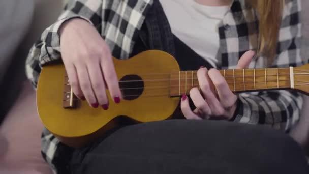 Detailní záběr mladé bělošky hrající ukulele. Dospívající dívka cvičí doma na kytaru. Hudba, hobby, životní styl.