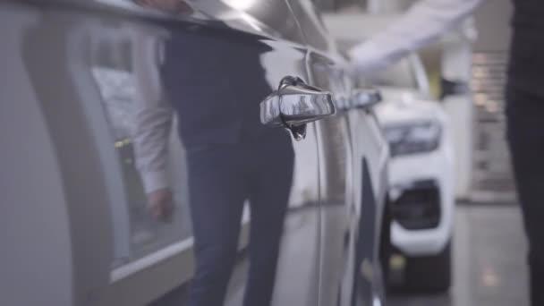 Nerozpoznatelný běloch v elegantním obleku přichází k automobilu a otvírá dveře od auta. Majitel si bere auto po opravě. Automobilový průmysl, záruční servis.