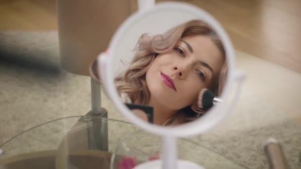Reflexe krásné bělošské dívky nanáší pudr na obličej. Zaměření se změní ze zrcadla na sadu make-upů. Životní styl, krása, péče o obličej.