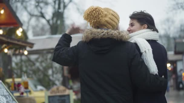 Back view of happy Caucasian couple standing on winter fair and talking. Young man showing something away, woman laughing. Cheerful spouses resting together outdoors. Lifestyle, unity, leisure.