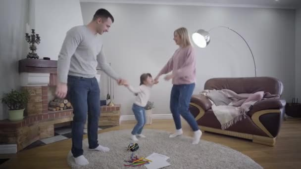 Cheerful young Caucasian family having fun indoors. Mother and father holding daughters hands, dancing and raising child up. Lifestyle, leisure, enjoyment.