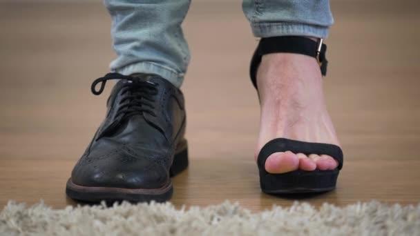 Extrémní detailní záběr bělošských nohou. Jednu nohu v pánské botě, druhou v dámské vysoké podpatkové botě. Intersexuální lidé, binární pohlaví.