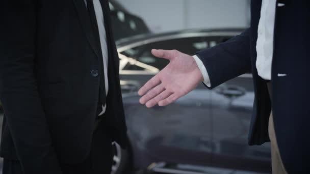 Detailní záběr dvou nerozpoznatelných bělochů, jak si potřásají rukou před automobily v prodejně aut. Potřesení rukou dealera a zákazníka. Automobilový průmysl, automobilový průmysl.